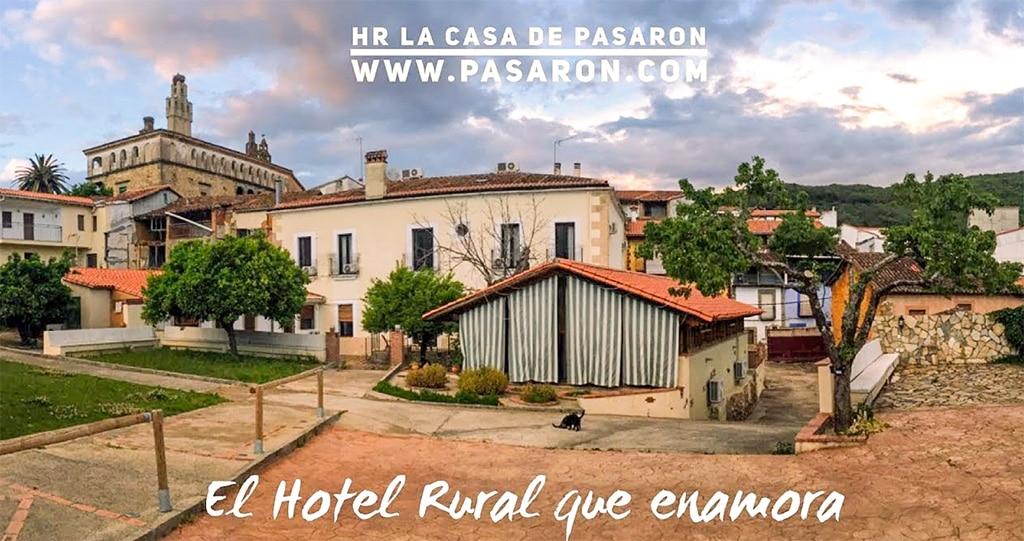 Vista desde el parking del hotel rural. Casa, salón social parte del jardín y al fondo, el palacio de Pasarón con sus características chimeneas.